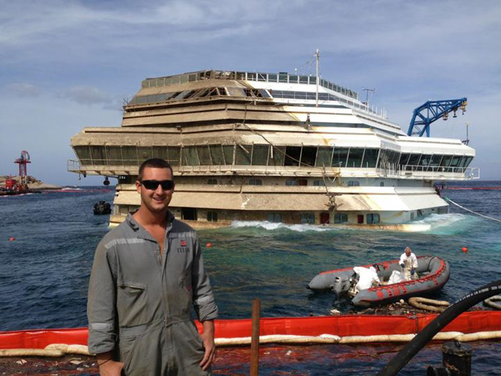 Student, Dylan standing in front of half-raised ship, Costa Concordia
