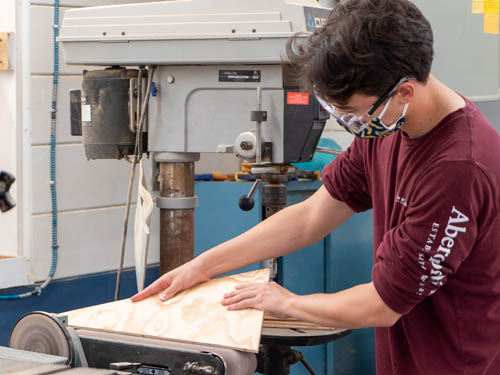 Student using the jigsaw machine at the Carpentry Shop