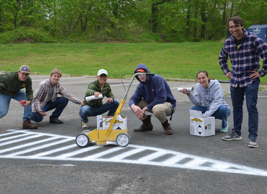 Students spray painting lines in the parking lot on Webb Institute's Founder's Day.